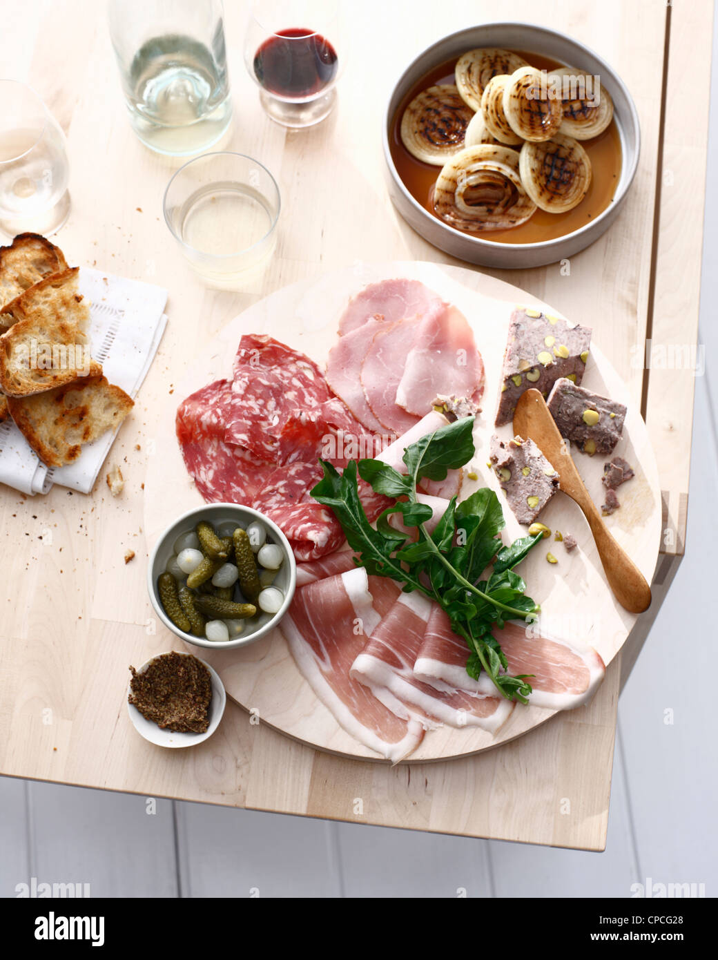 Plate of sliced meats, bread and herbs - Stock Image