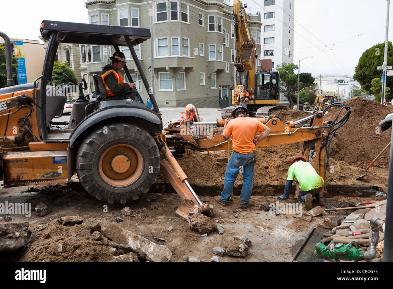 Municipal construction workers and backhoe digging trench - Stock Image