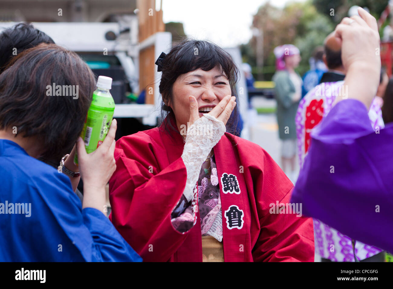 A Japanese woman covering her mouth while laughing - Stock Image