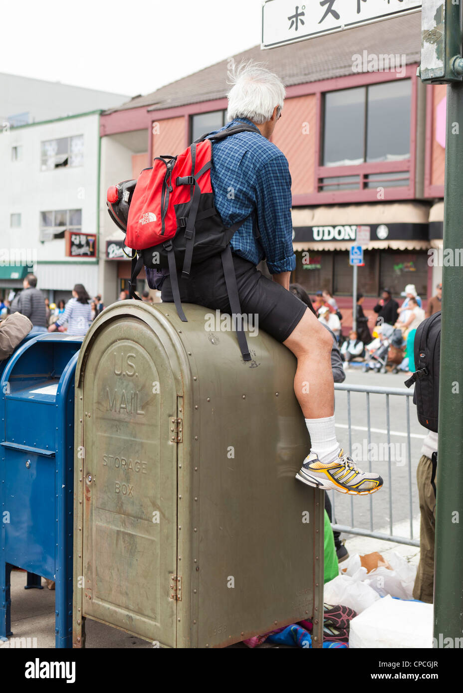 A man sitting on a mailbox - Stock Image