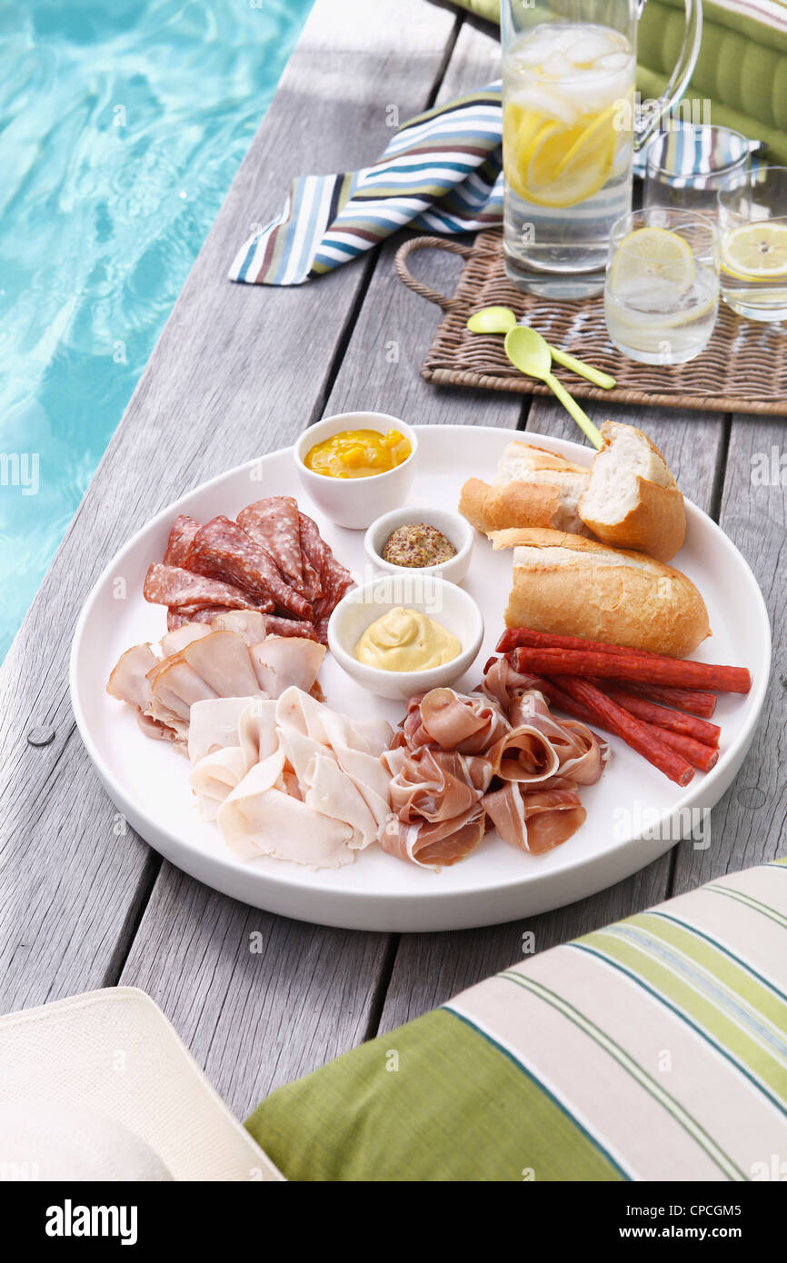 Plate of sliced meats, bread and mustard - Stock Image