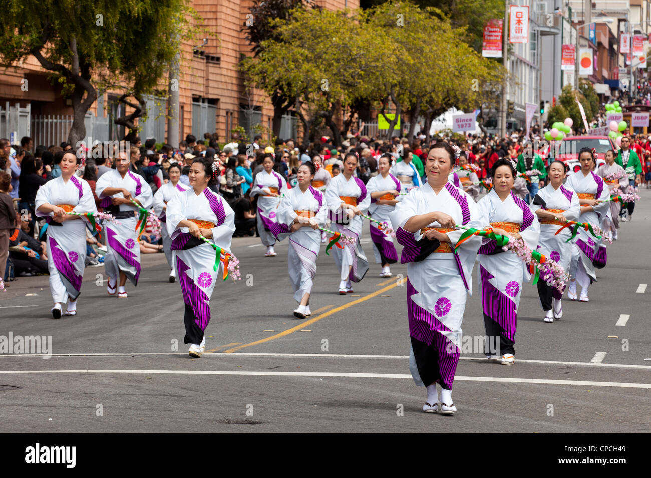 Japanese women performing traditional dance in a parade - Stock Image