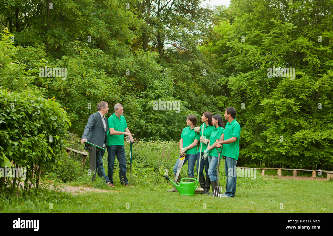 Gardeners with businessman in park - Stock Image