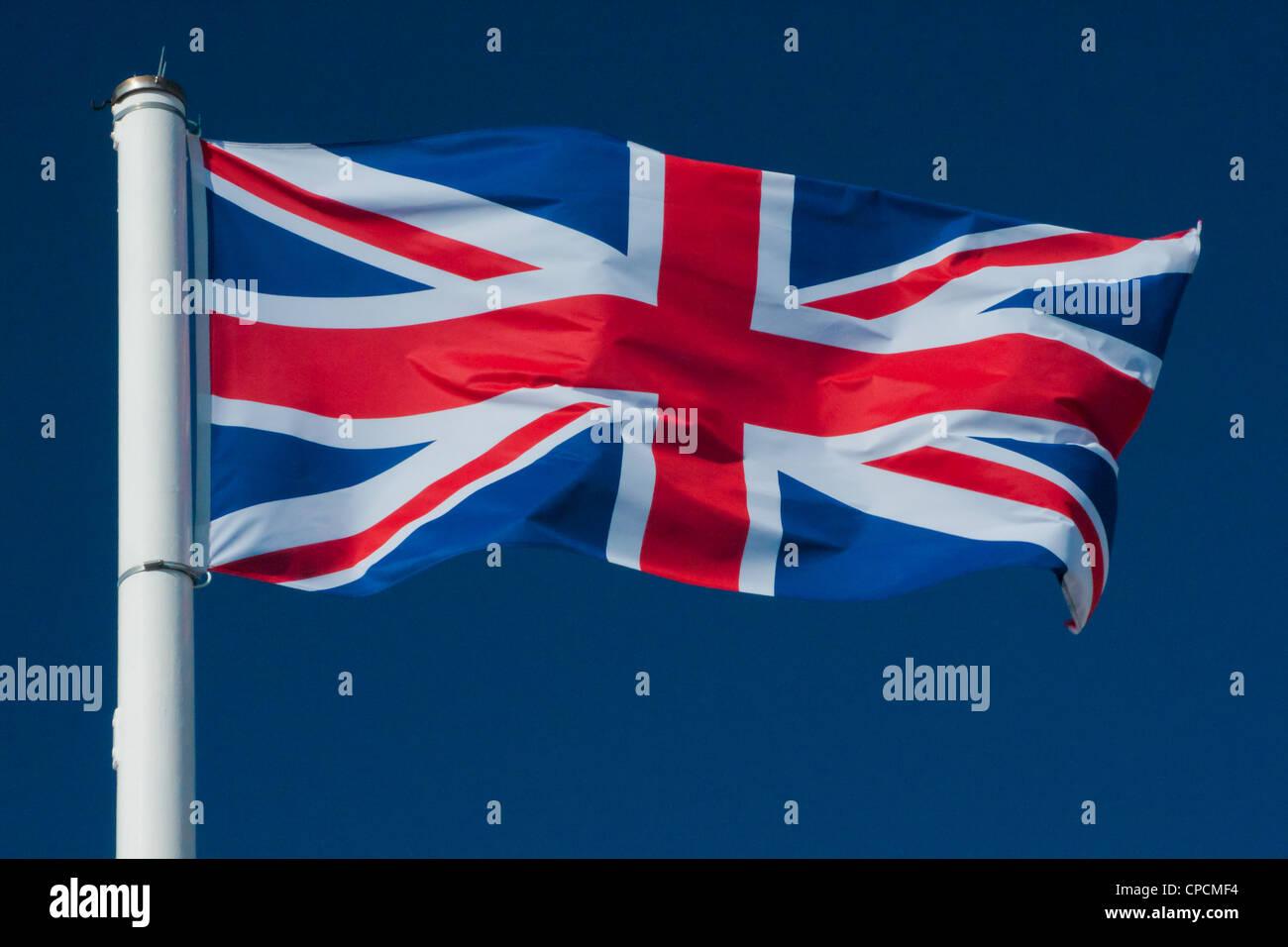 Union Jack Flag Flying with Blue Background - Stock Image