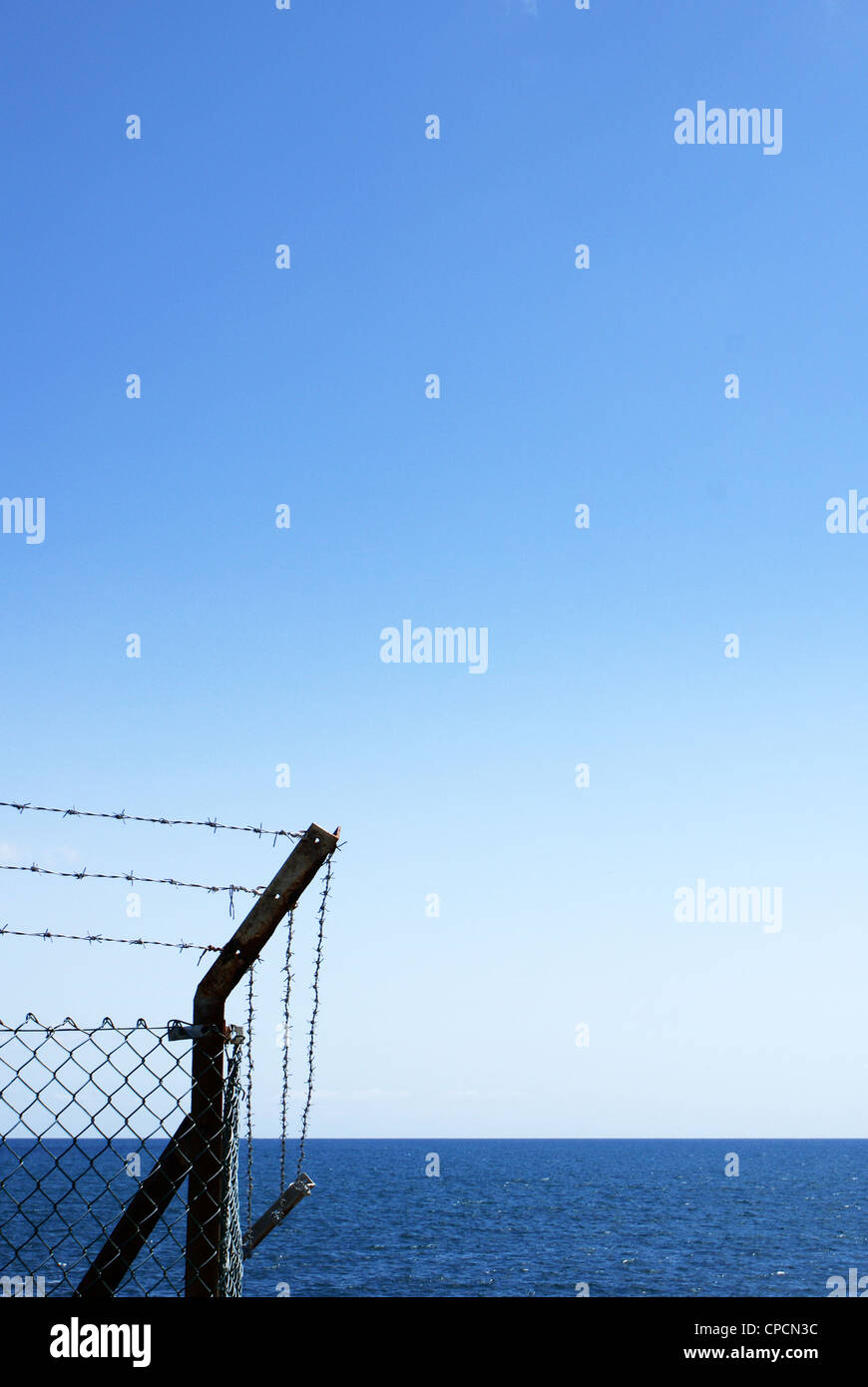 Barb wired fence by the sea - Stock Image
