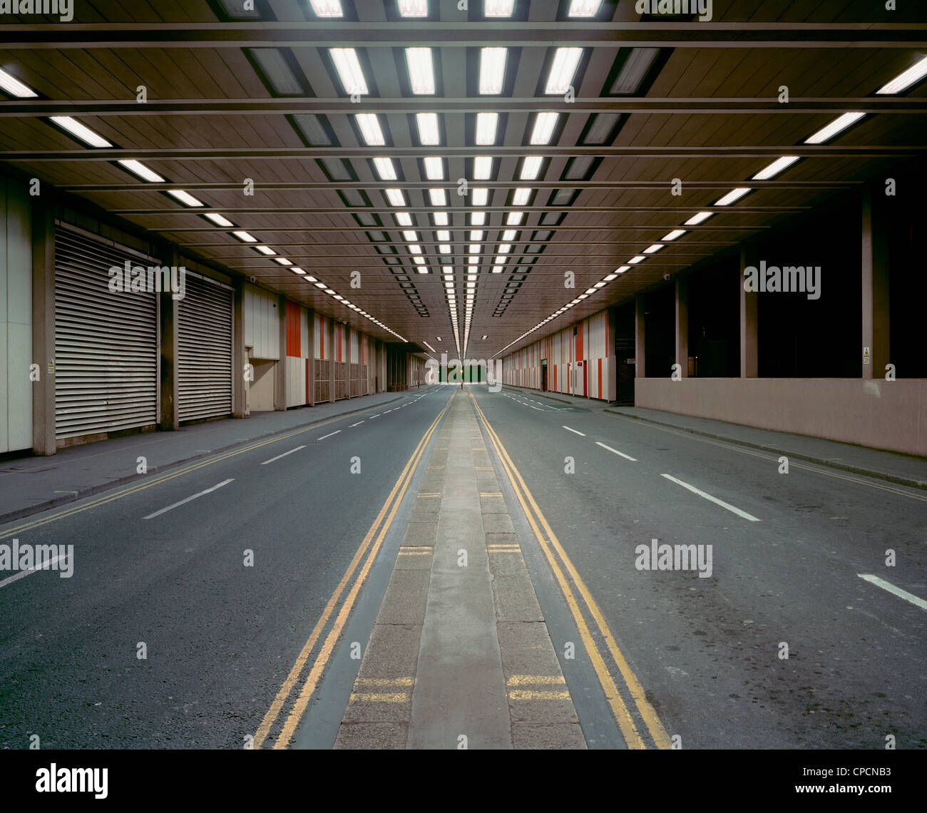 Illuminated road in parking structure - Stock Image