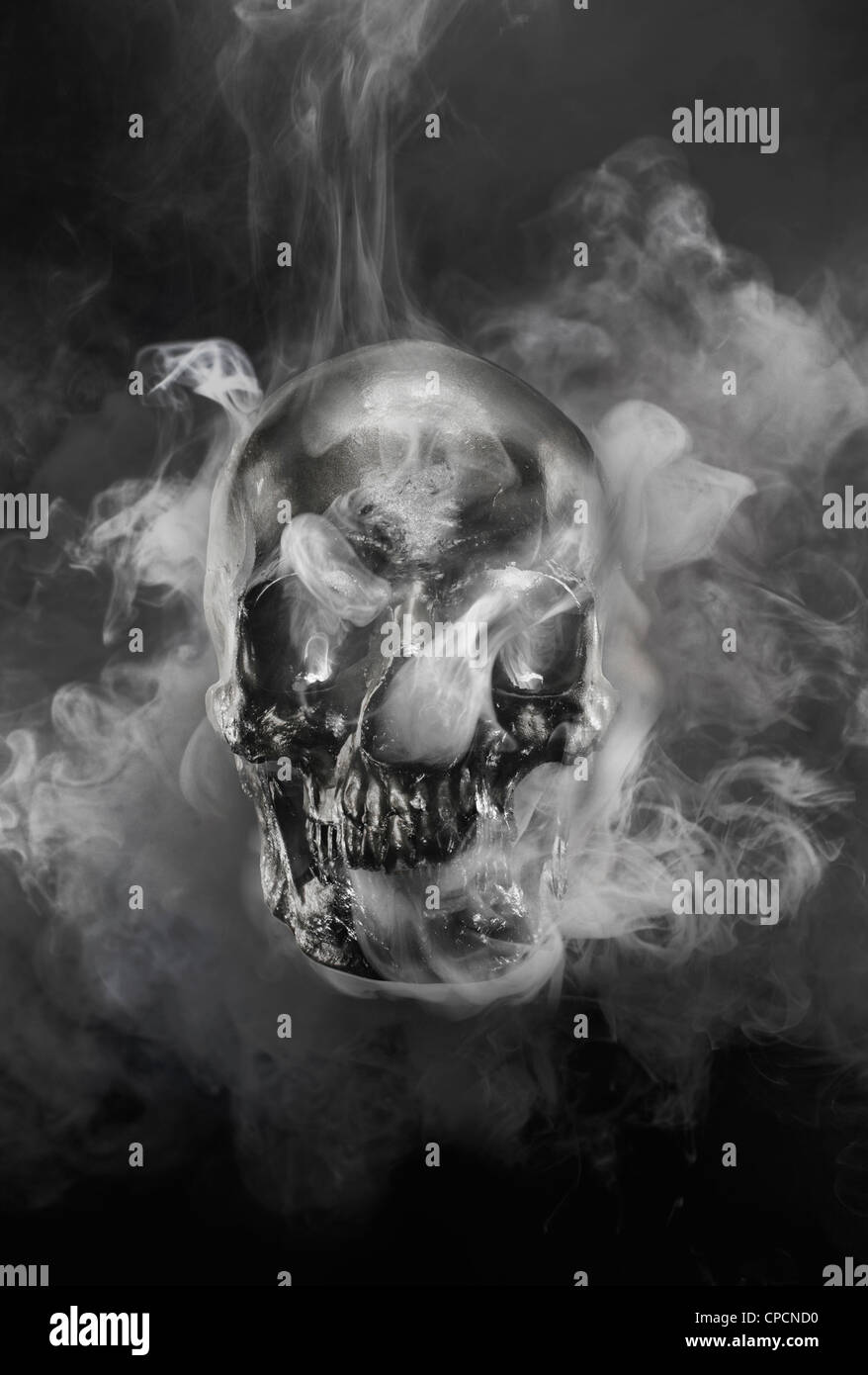 Smoke pouring from metal skull - Stock Image