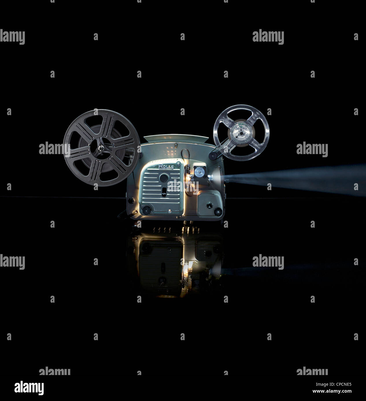 Glowing movie projector with reel - Stock Image