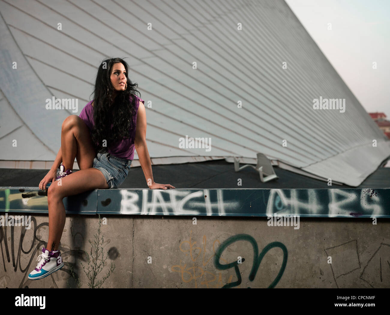 Woman sitting on gratified wall - Stock Image