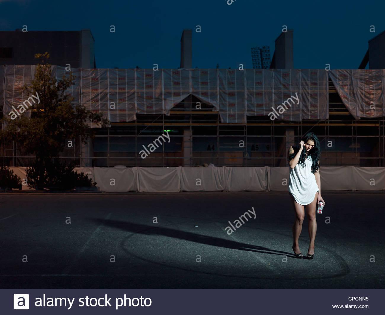 Woman walking in city at night - Stock Image