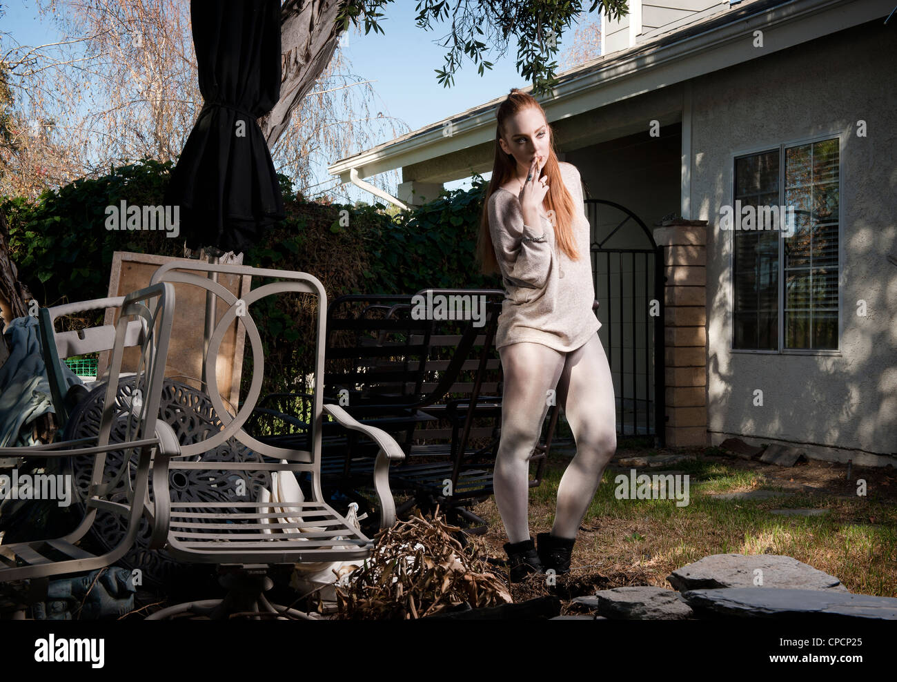 Woman standing in dilapidated backyard - Stock Image