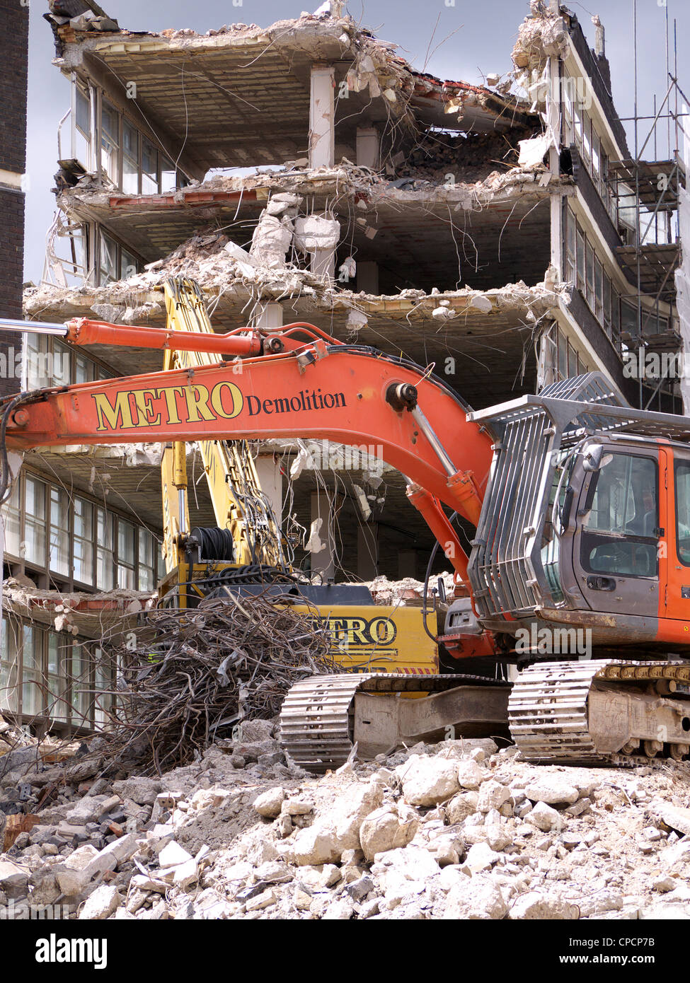 Excavators knocking down and old building in London UK - Stock Image