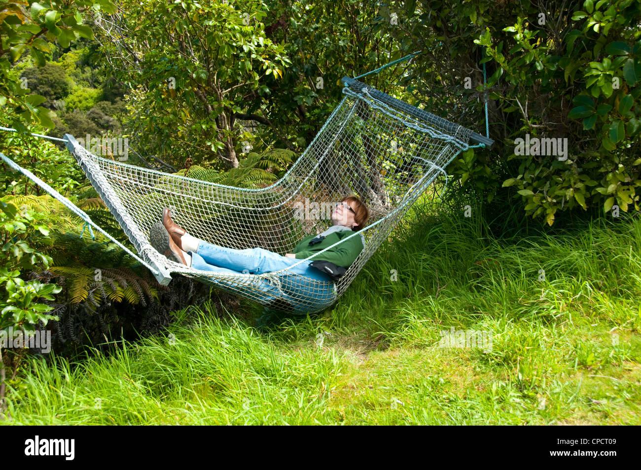 New Zealand South Island, woman in hammock at Picton lodge resort Lochmara - Stock Image