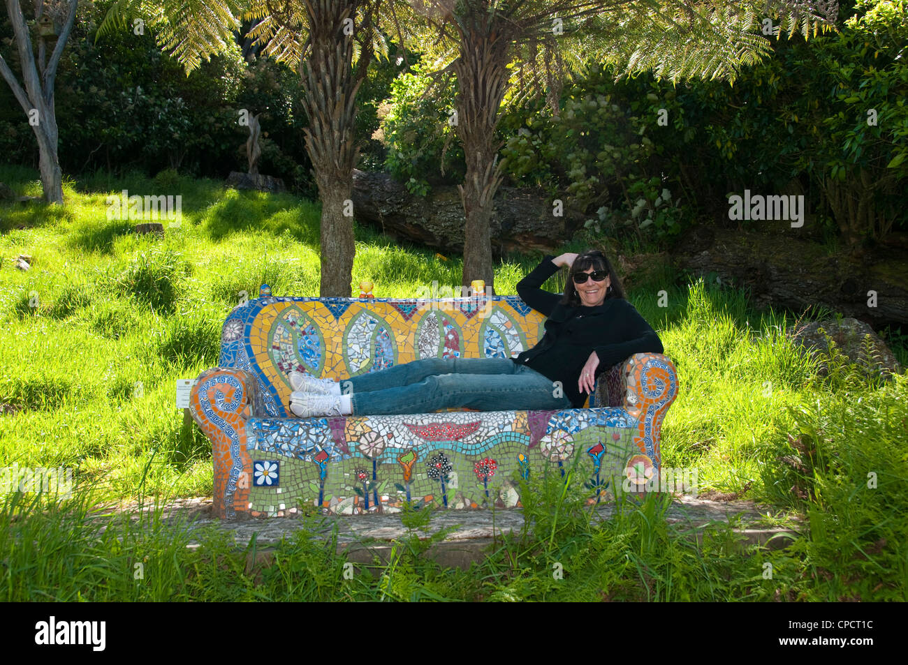 New Zealand South Island woman relaxing at lodge resort Lochmara on colorful stone artistic couch - Stock Image