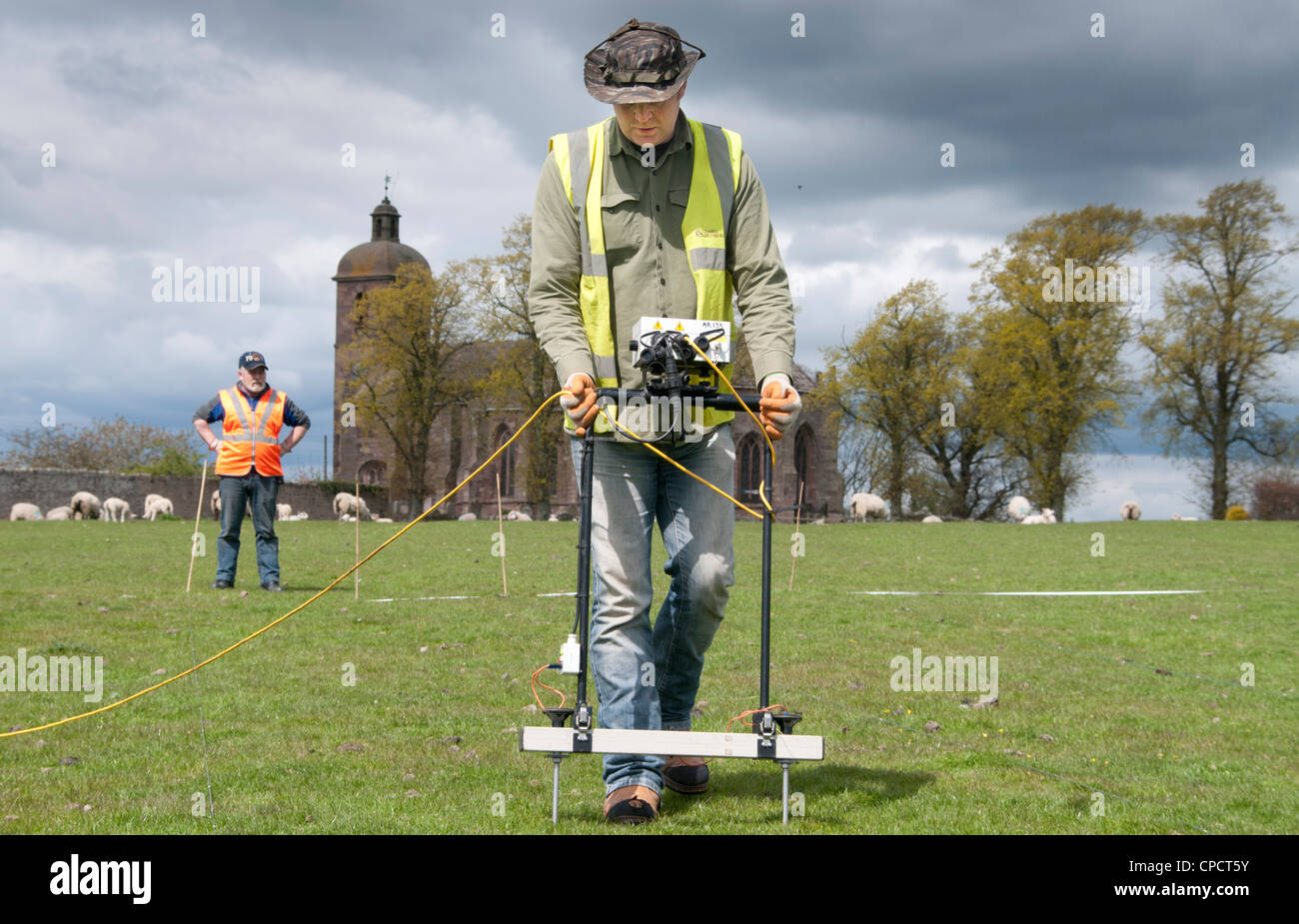 An archaeologist near Ladykirk overlooking the Scottish Border in to England carrying out a shallow geophysics survey - Stock Image