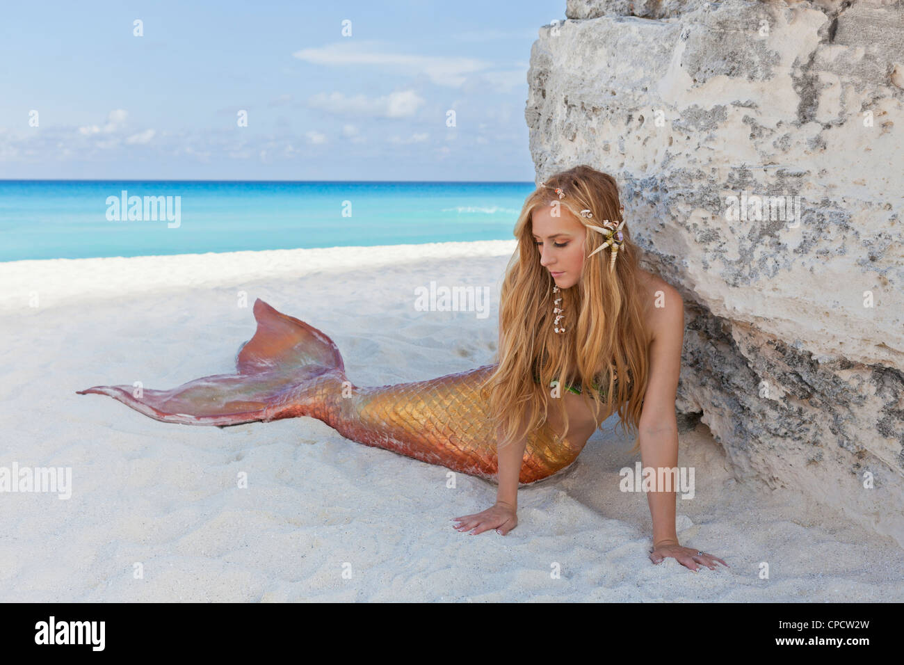 Young blond mermaid laying on the beach in Cancun, Mexico - Stock Image