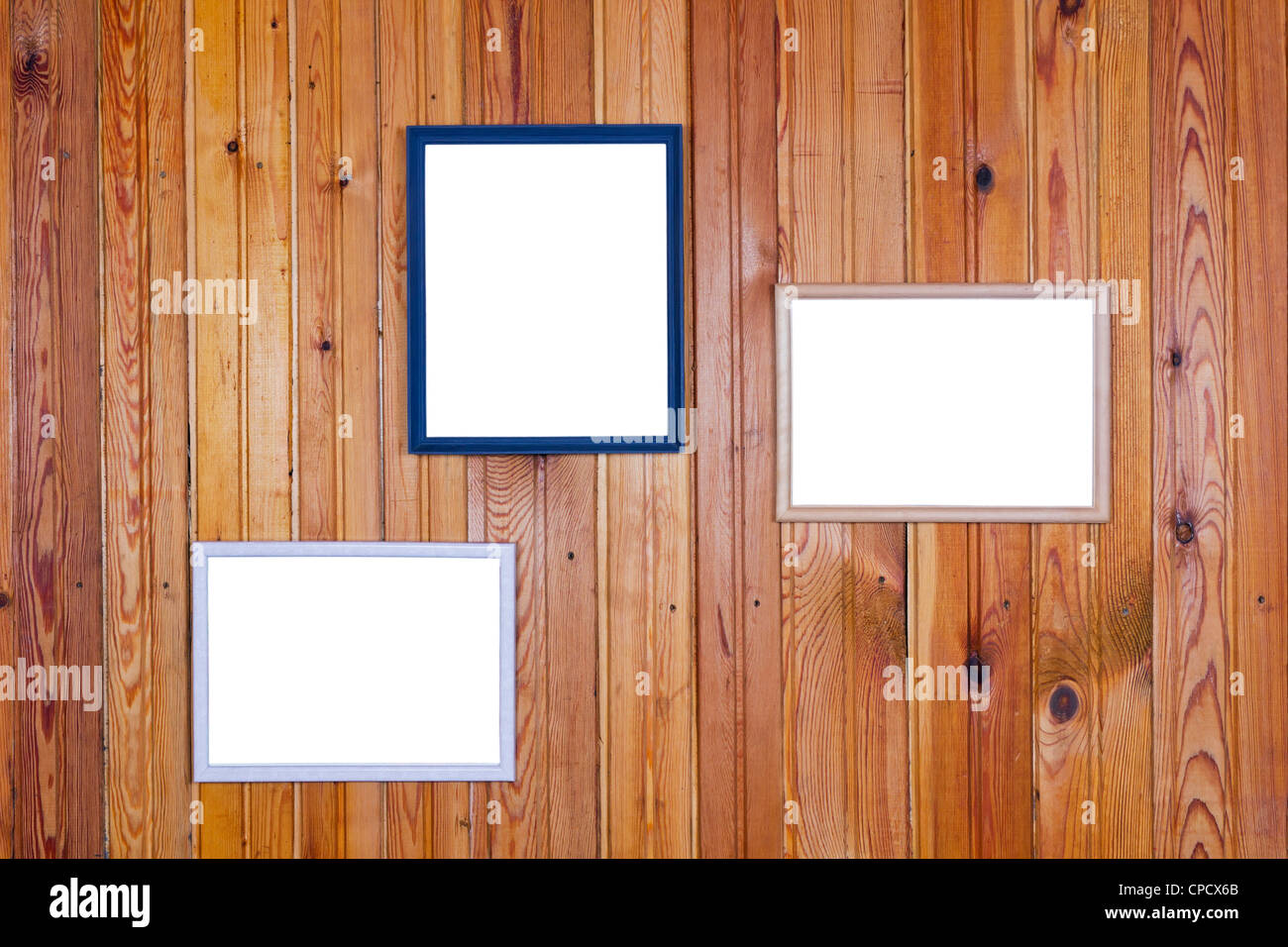 On the old yellow rural home wall of pine wood planks hung empty white pictures frames - Stock Image