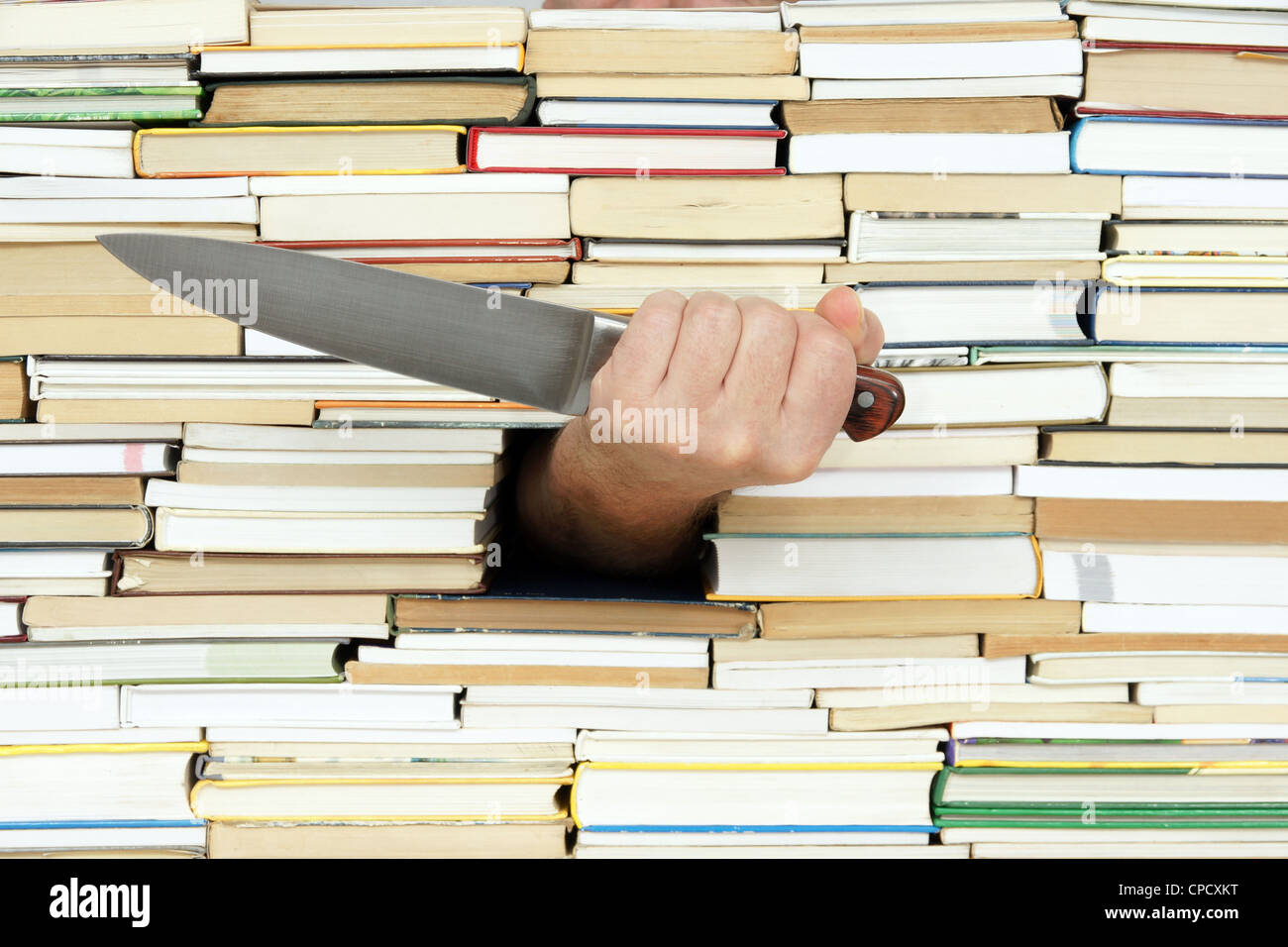big kitchen knife in hand on background of books - Stock Image
