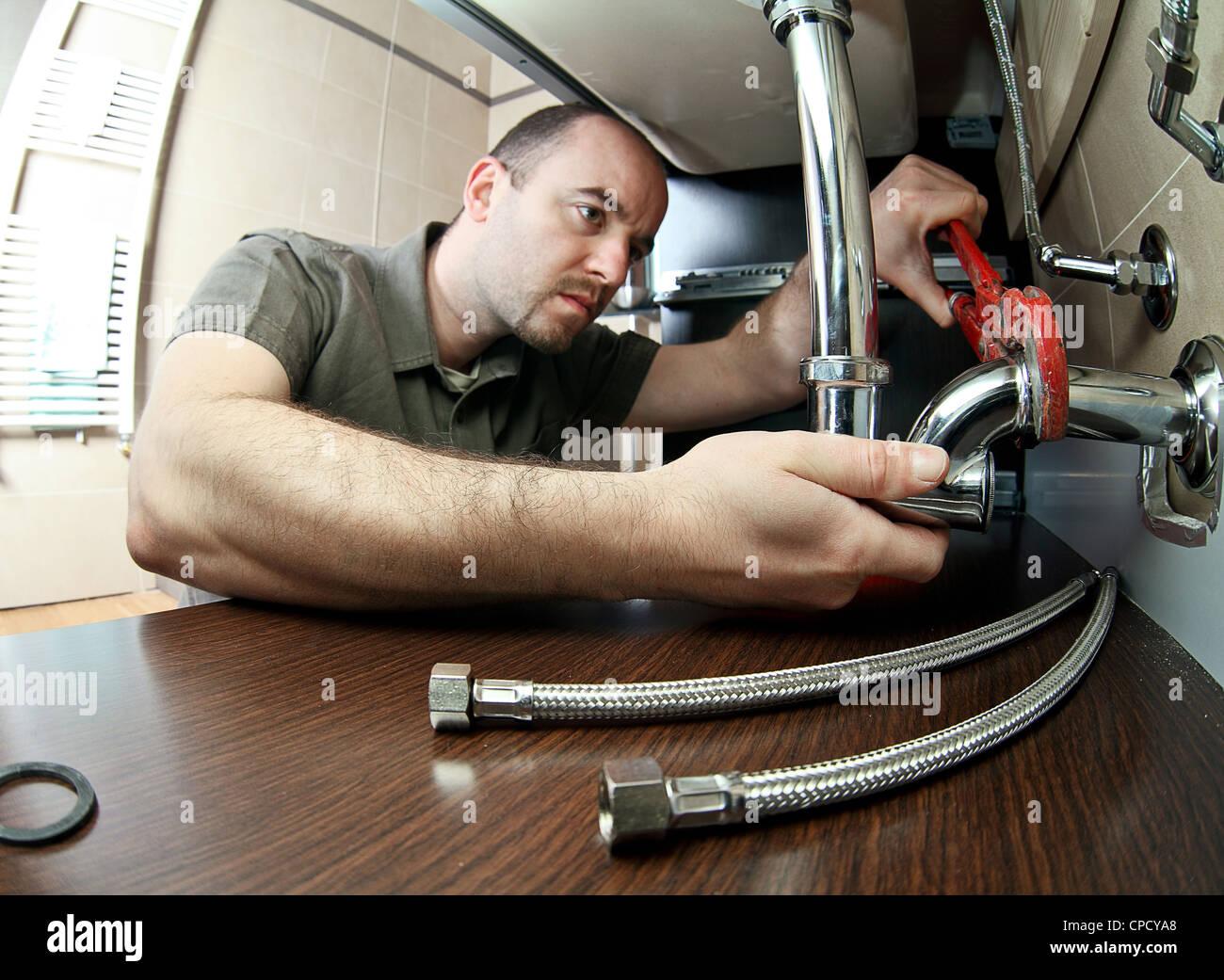 closeup image of young plumber at work - Stock Image
