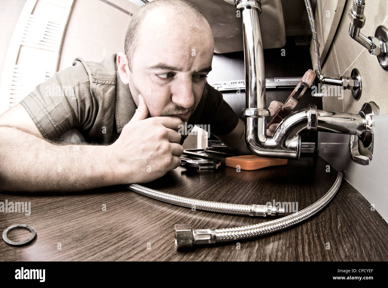 plumber thinking how to fix - Stock Image