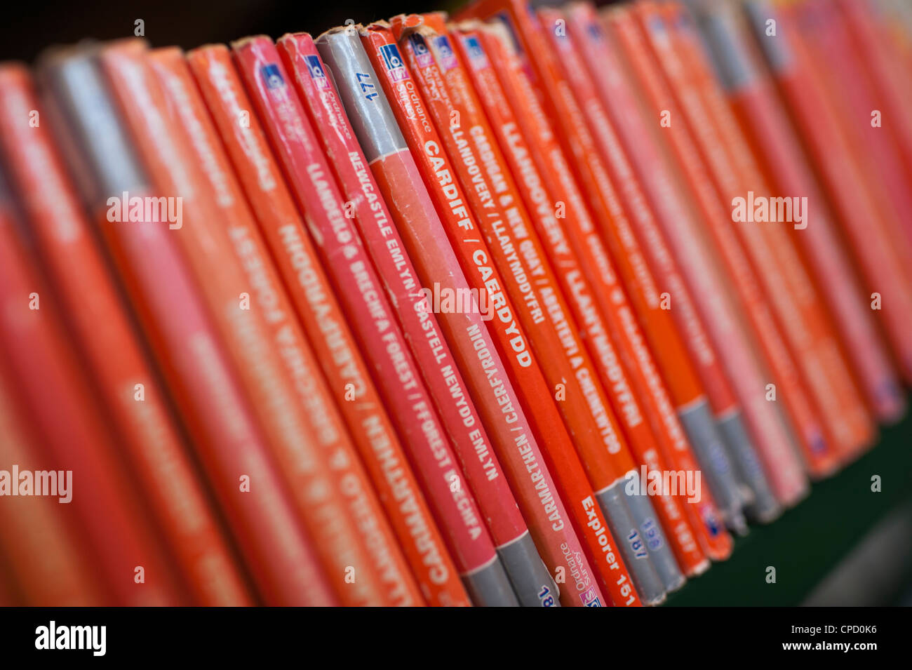Orange spines of british Ordnance Survey Explorer series maps in the reference section of a public library, UK - Stock Image
