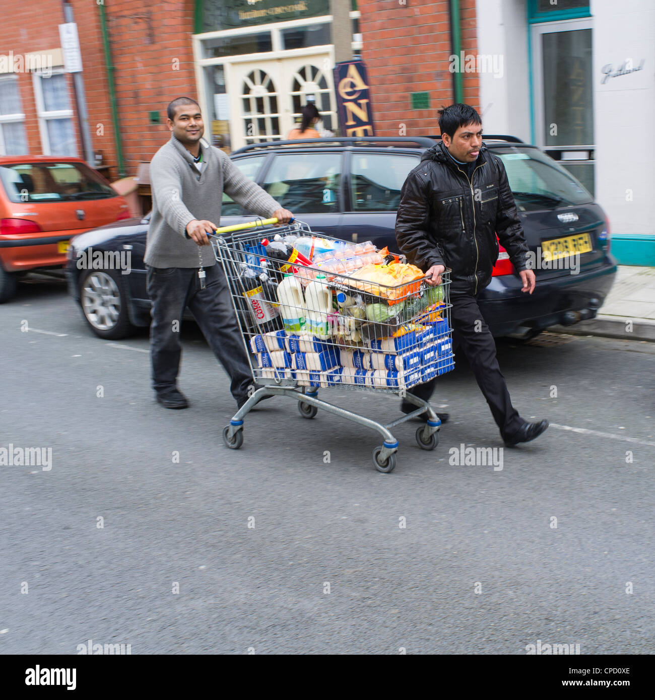 Two young men pushing a shopping trolley full of food down a street, UK - Stock Image