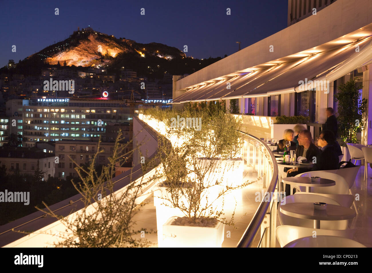 Rooftop terrace bar at the Athens Hilton with Lykavittos Hill illuminated at night, Athens, Greece, Europe - Stock Image