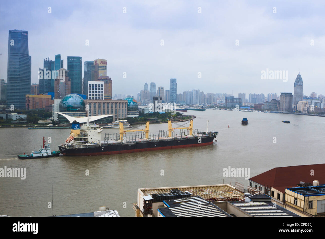 Large transport ship and tug on the Huangpu River that runs through Shanghai, China, Asia - Stock Image