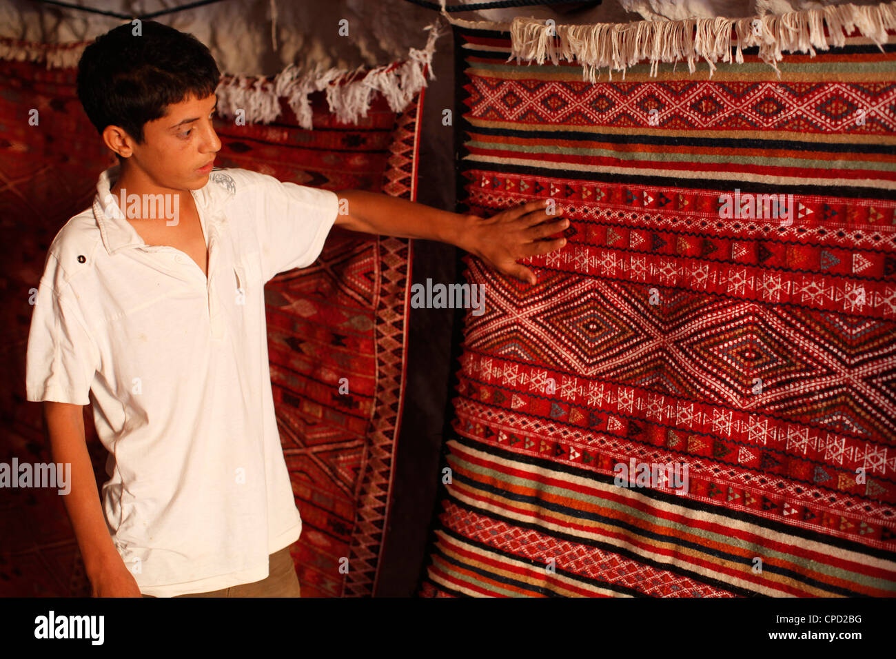 Boy showing a rug in a carpet shop, Toujane, Tunisia, North Africa, Africa - Stock Image