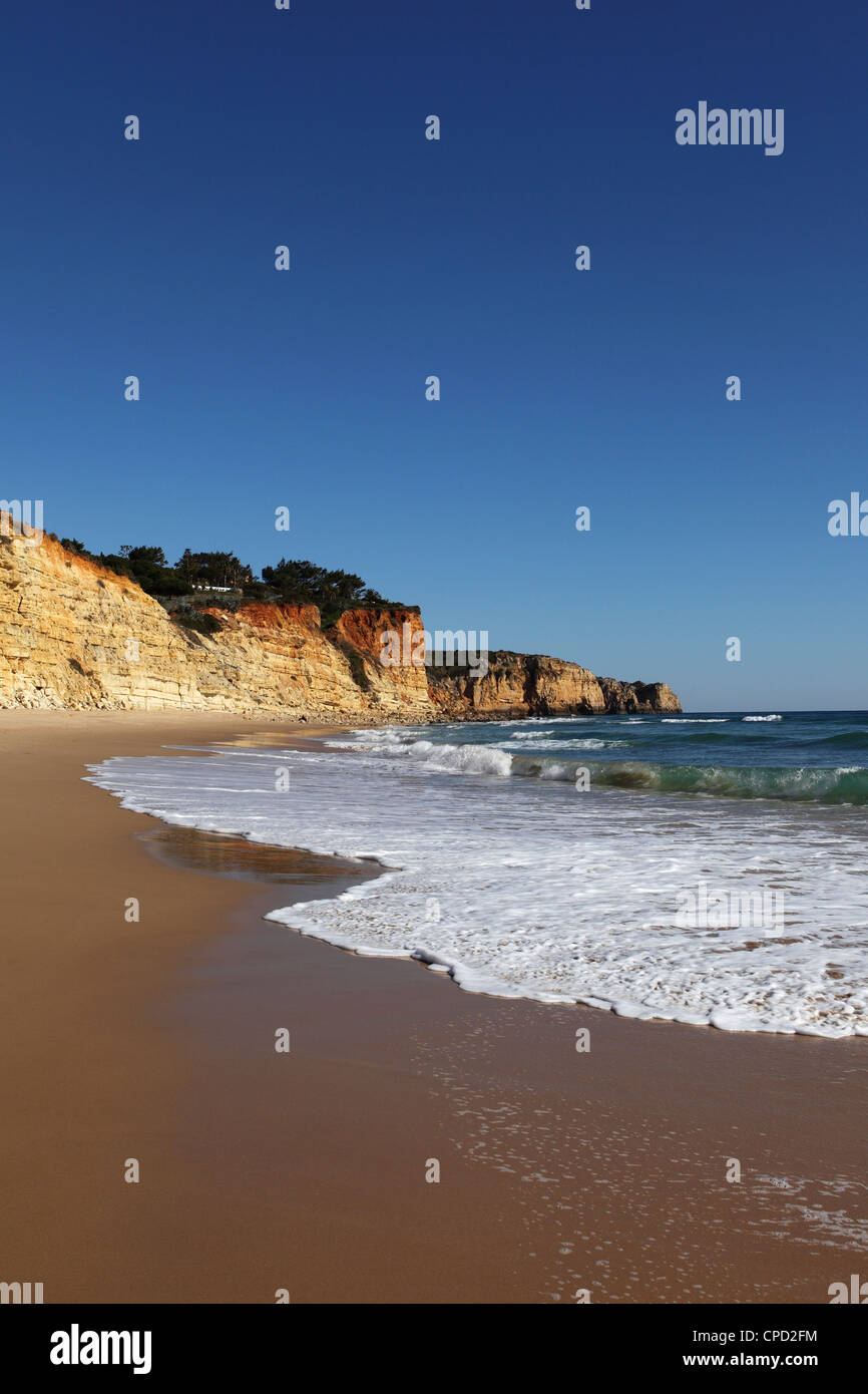 A wave breaks on golden sands flanked by steep cliffs, typical of the Atlantic coastline near Lagos, Algarve, Portugal, - Stock Image