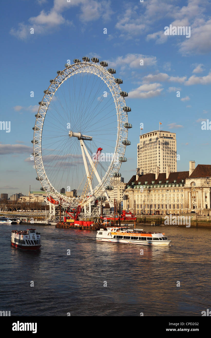 Cruise boats sail past County Hall and the London Eye on the South Bank of the River Thames, London, England, United - Stock Image