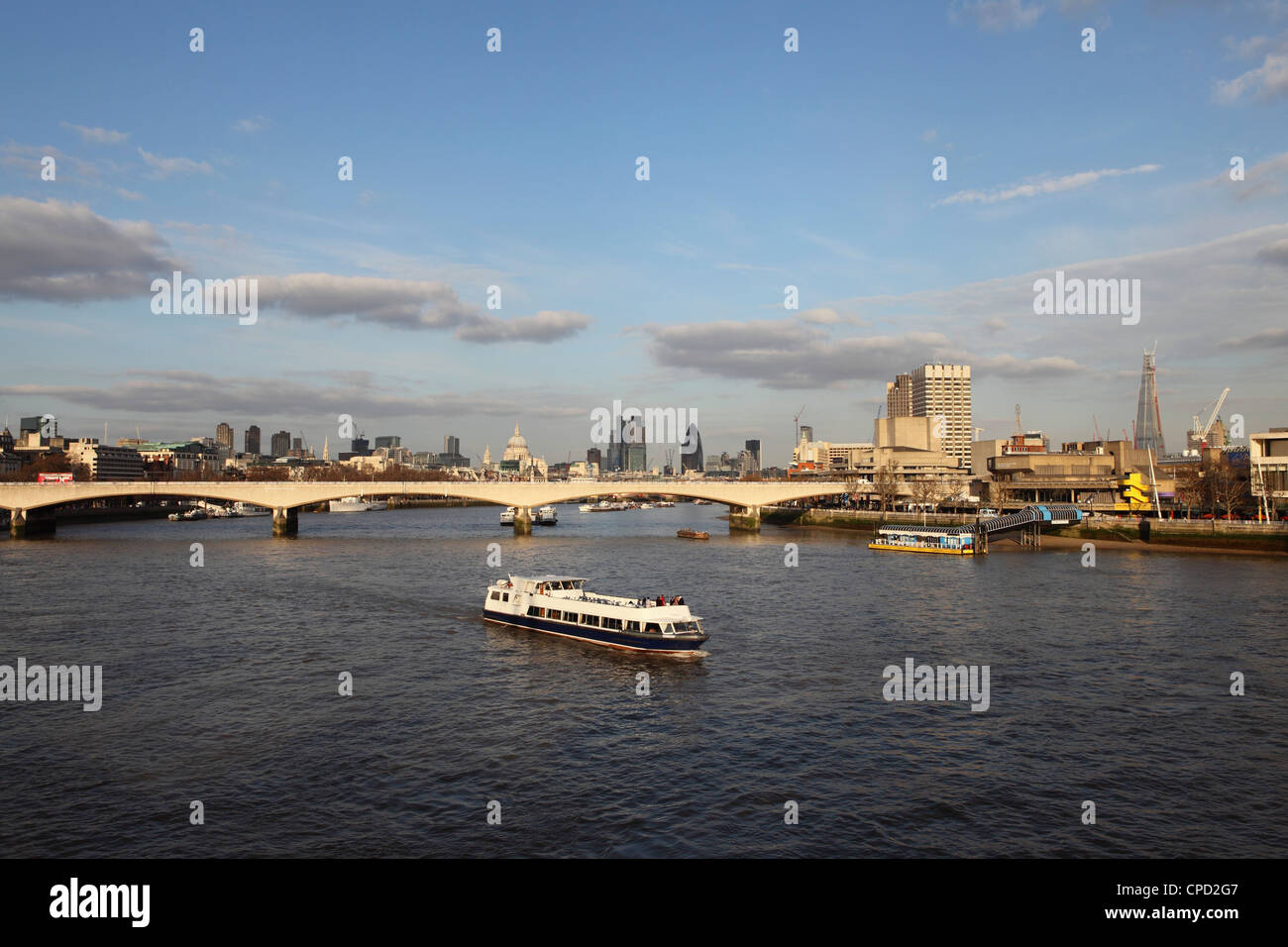 A cruise boat on River Thames, ahead of Waterloo Bridge and the skyline of the City, from Westminster, London, England, Stock Photo