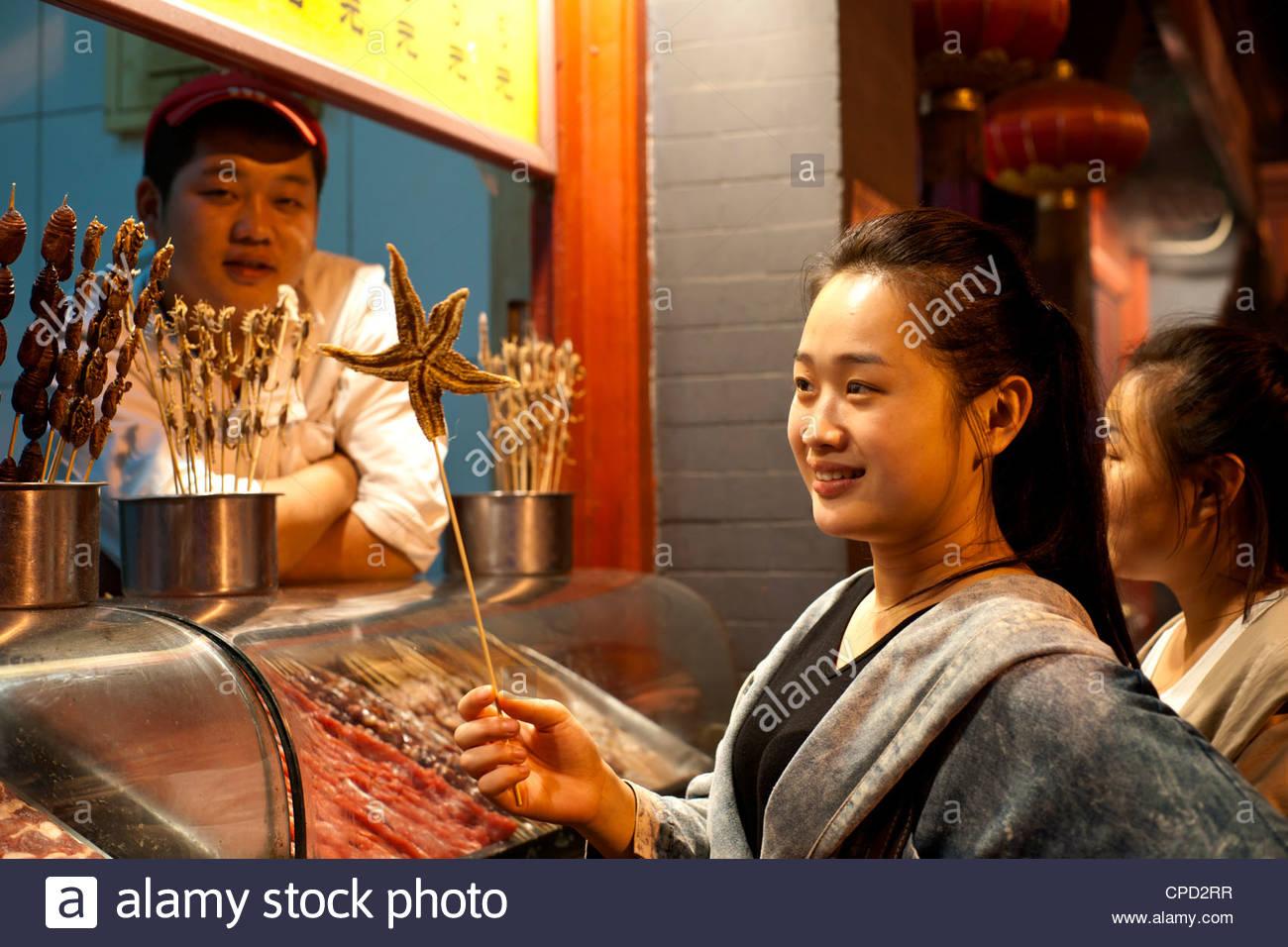 Woman purchasing a starfish on a stick at the Night Market, Wangfujing, Beijing, China, Asia - Stock Image