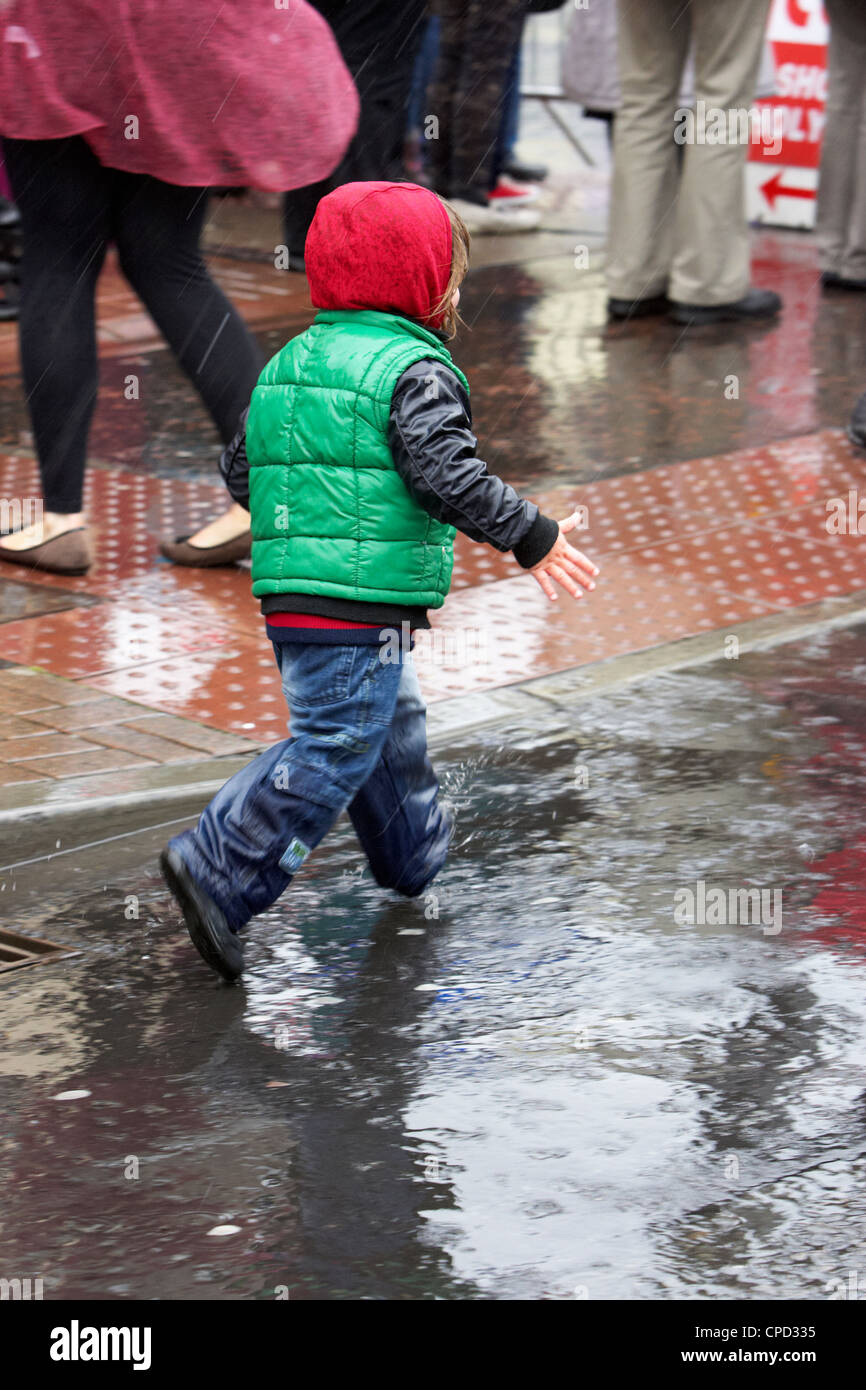 young boy splashing through puddles in a rain shower in the uk - Stock Image