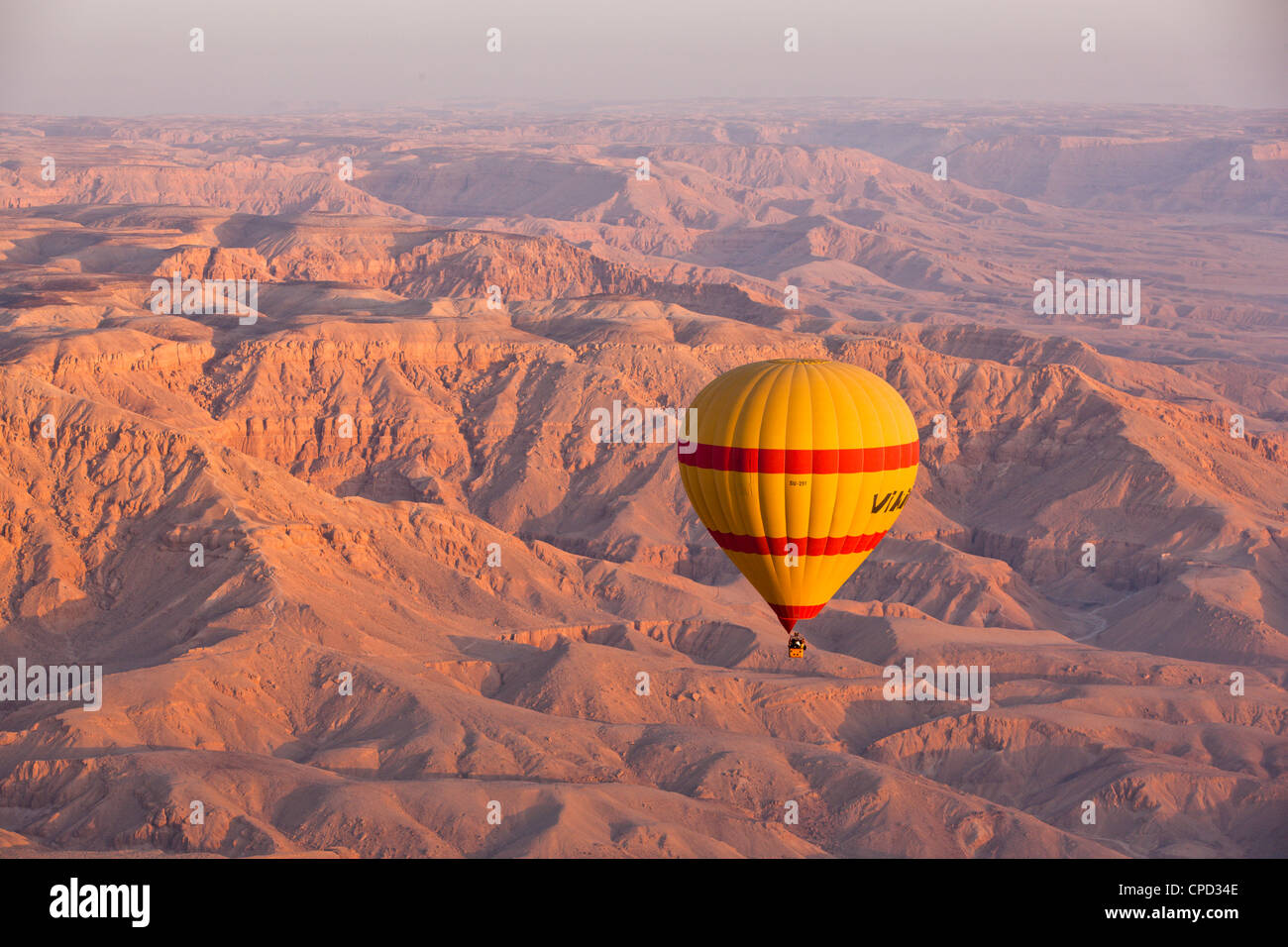 Hot air balloon suspended over the Theban hills of Luxor at sunrise, Thebes, Egypt, North Africa, Africa - Stock Image