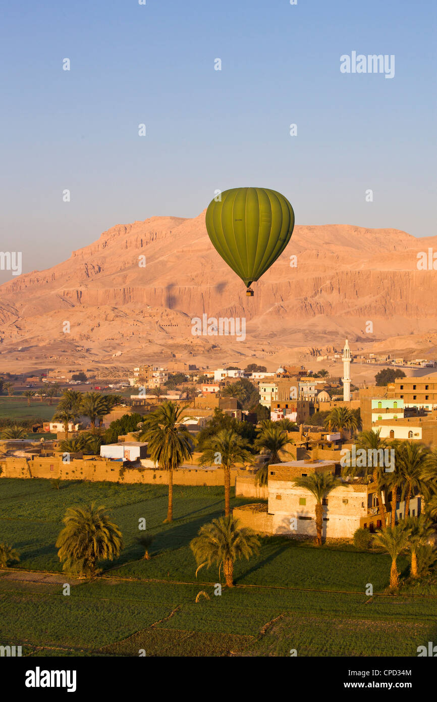 Hot air balloon suspended over the Theban necropolis and houses of Luxor, Thebes, Egypt, North Africa, Africa - Stock Image