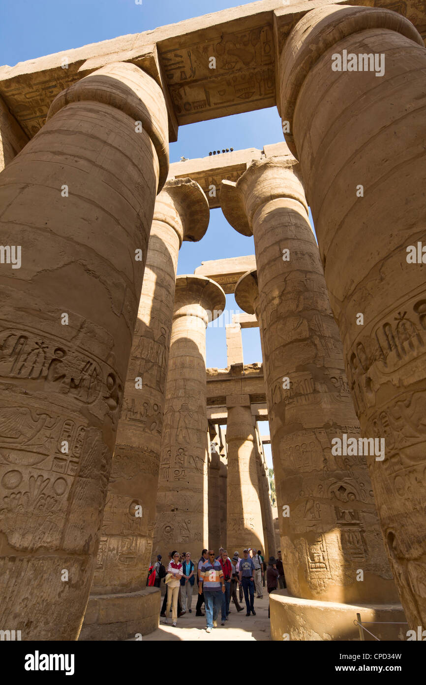 Tourists dwarfed by the towering columns of the Great Hypostyle Hall of the Karnak Temple of Amun, Thebes, Egypt, - Stock Image