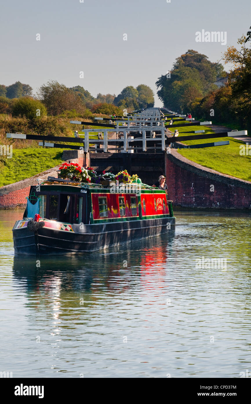 A canal boat leaving the famous series of locks at Caen Hill on the Kennet and Avon Canal, Wiltshire, England, United - Stock Image
