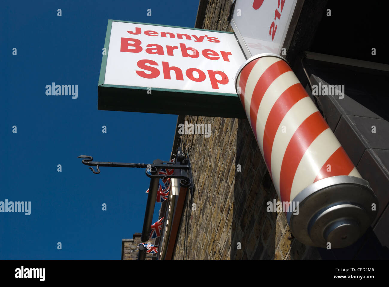 barber's shop sign with traditional red and white revolving pole, east sheen, southwest london, england - Stock Image