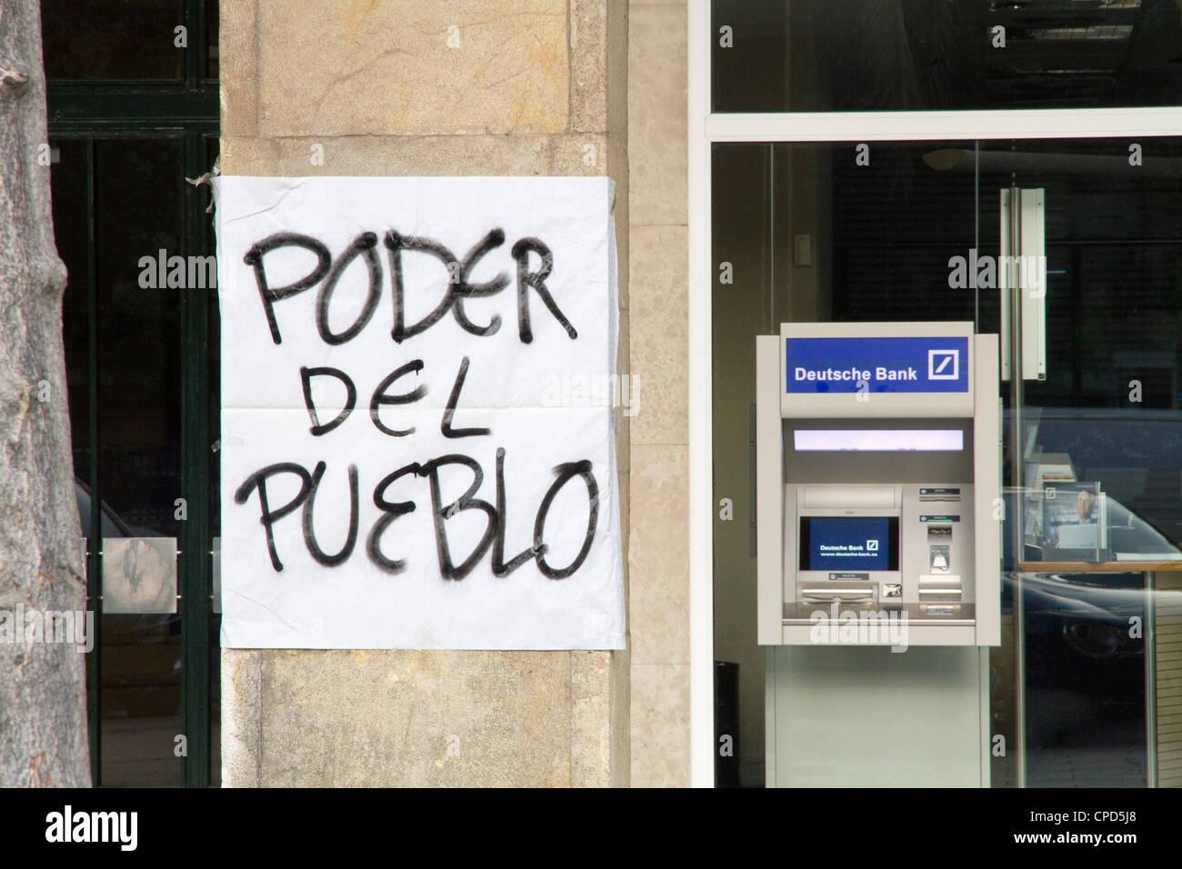 Protest message 'Power to people''poder del pueblo' near the deutsche Bank cash machine Spain - Stock Image
