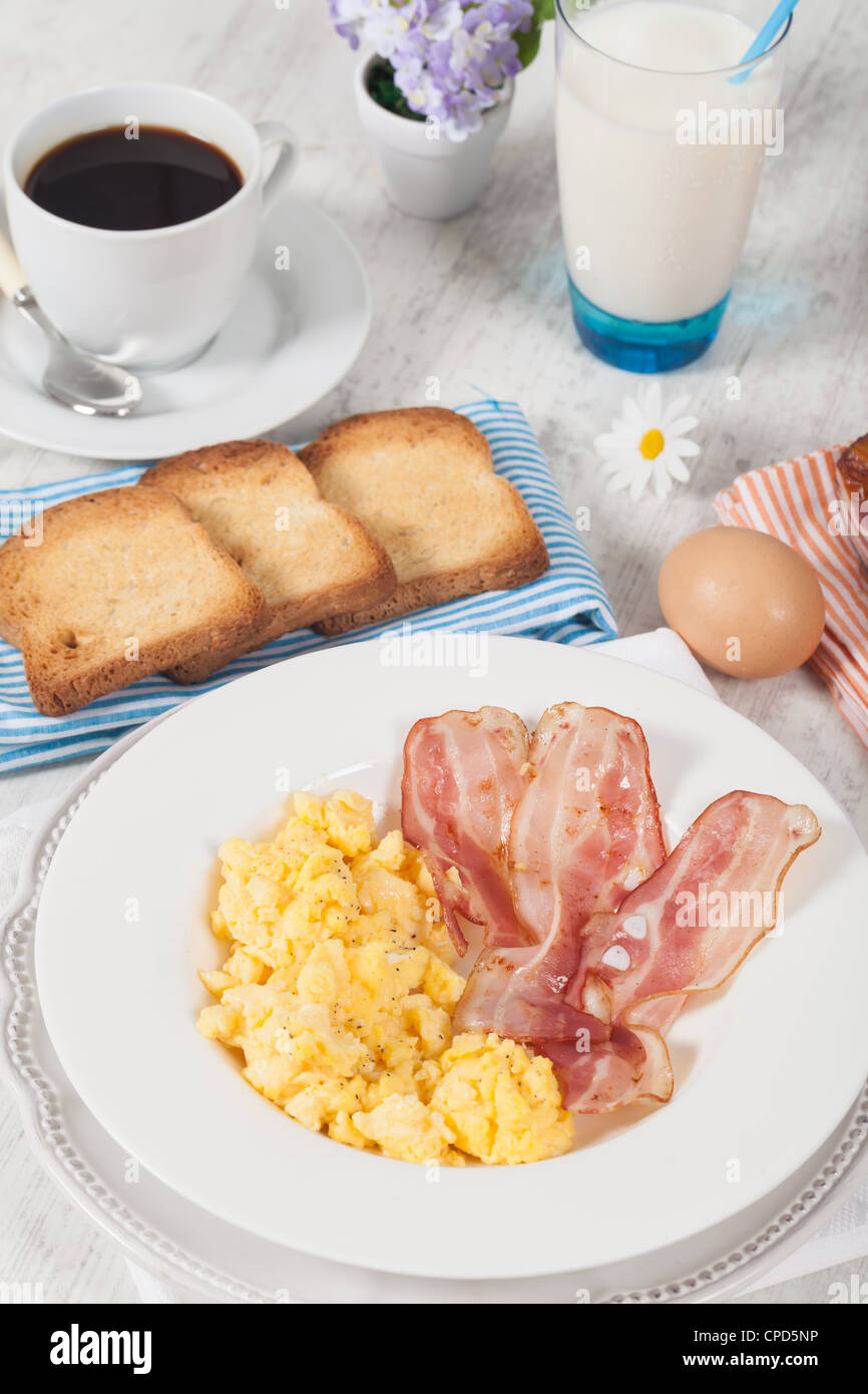 Breakfast with scrambled eggs and crispy bacon - Stock Image