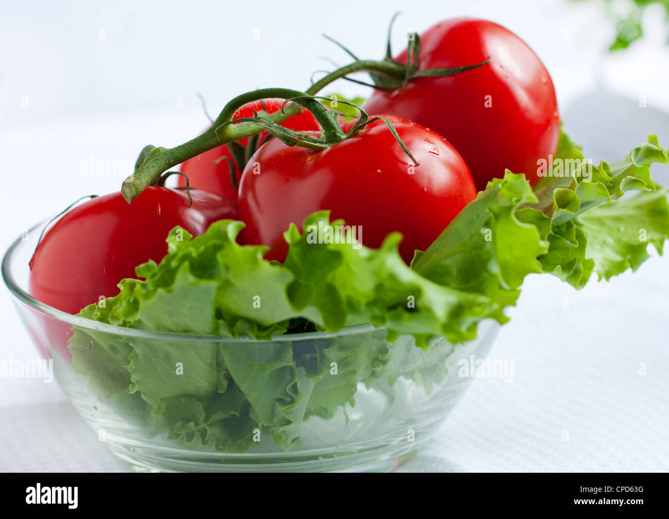 Red tomatoes in a transparent round salad bowl - Stock Image