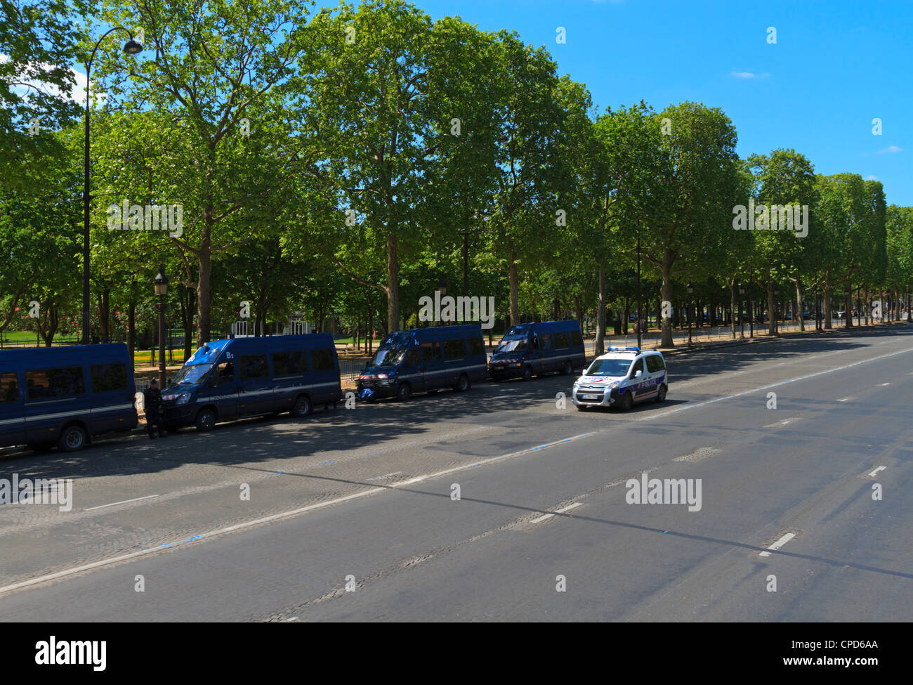 Gendarmerie vans parked on the Champs Elysee and a police car passing, Paris - Stock Image