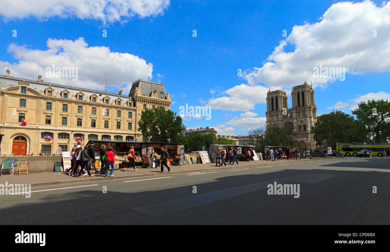 Left Bank, Paris, the Prefecture de Police and Notre Dame Cathedral. Tourists look at vendors kiosks on a sunny - Stock Image