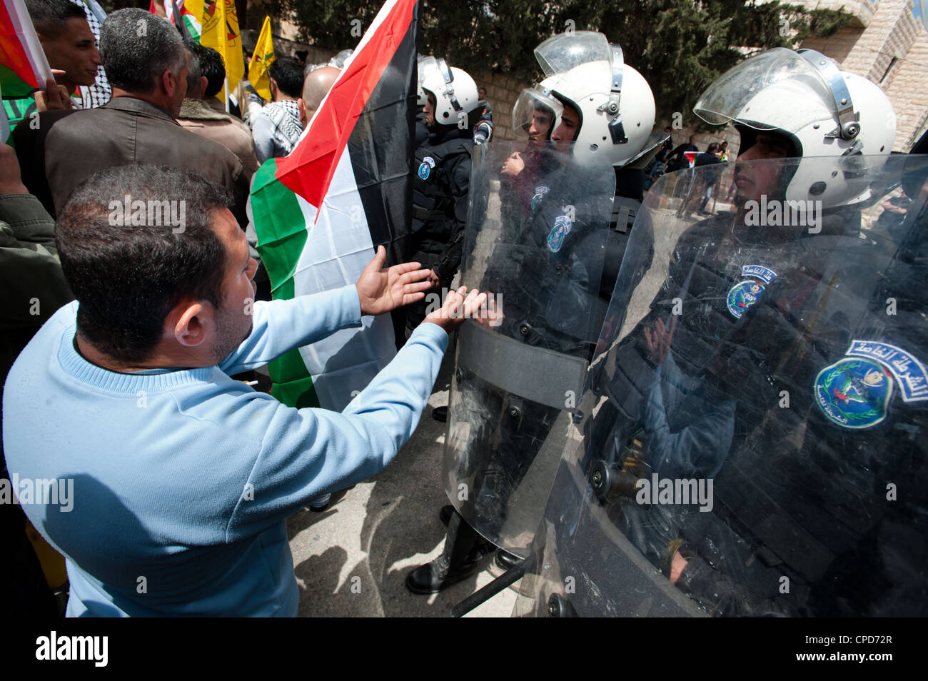 Palestinian protesters confront riot police of the Palestinian Authority during Land Day protests. - Stock Image