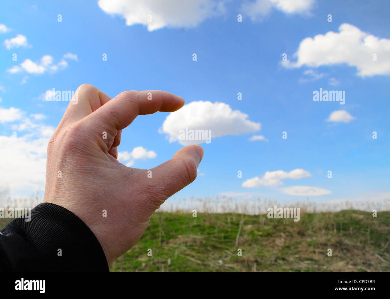Human hand reaching for a cloud and grabing it Stock Photo