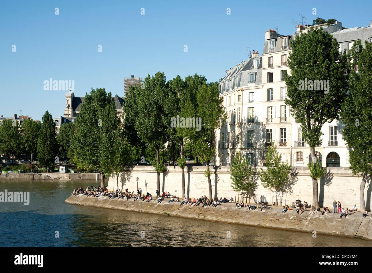 Paris, France  - People sunbathing on Ile St Louis - Stock Image