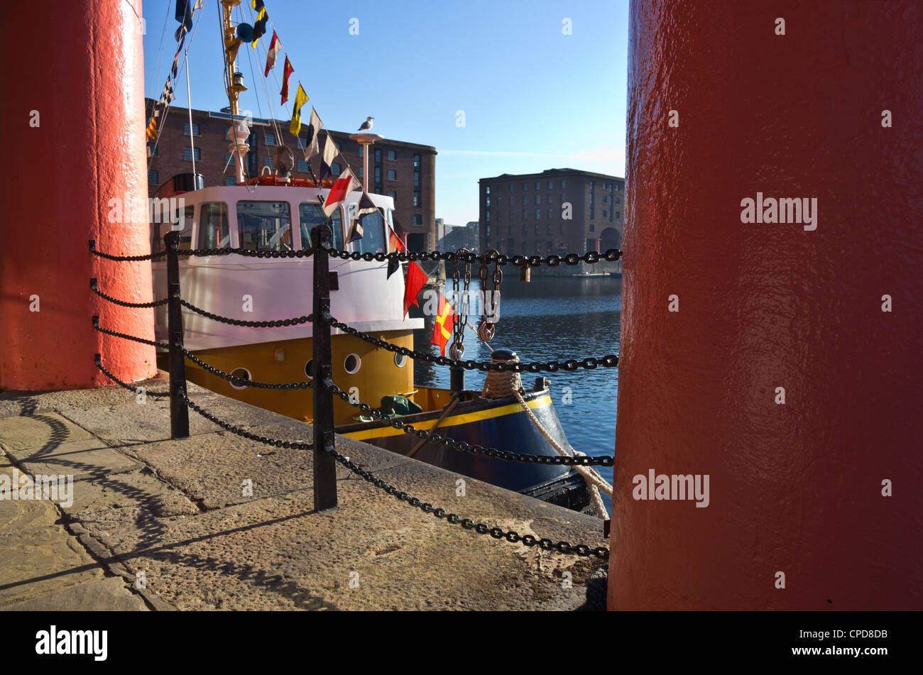 Albert Dock Pier Head Liverpool with pink columns warehouse buildings iron chain railings and brightly coloured - Stock Image