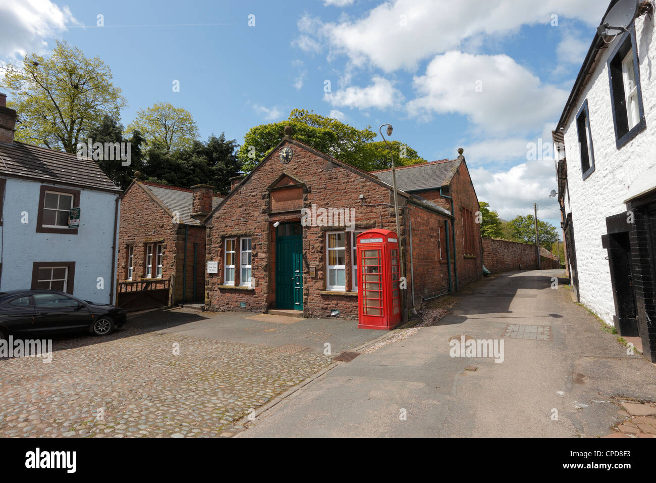 Church Institute with red telephone box in Croft Place, Kirkoswald in the Eden Valley Cumbria, England, UK - Stock Image