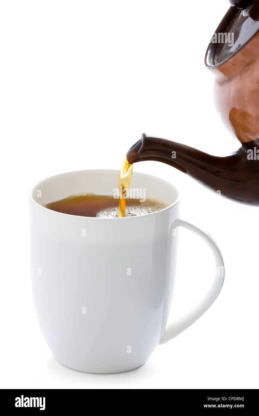 pouring tea from a tea pot into a white cup - Stock Image